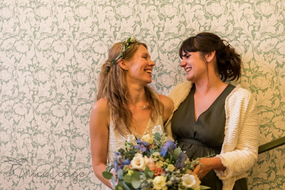 bride and maid of honour smiling at each other
