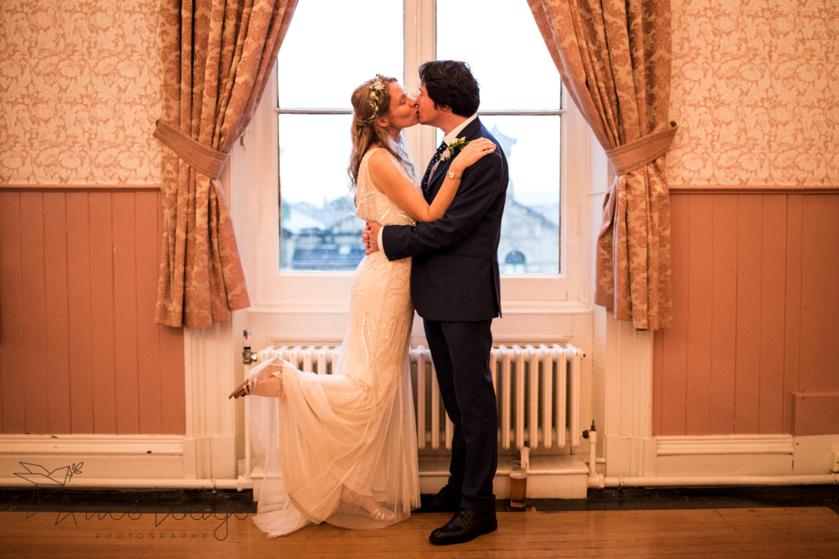 bride and groom kissing in front of window at Victoria Hall Saltaire
