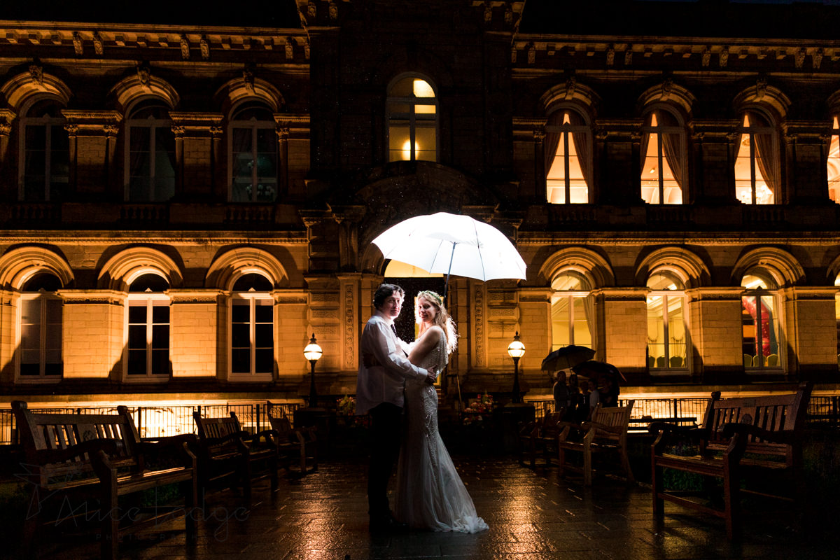 bride and groom in rain at night in front of Victoria Hall Saltaire
