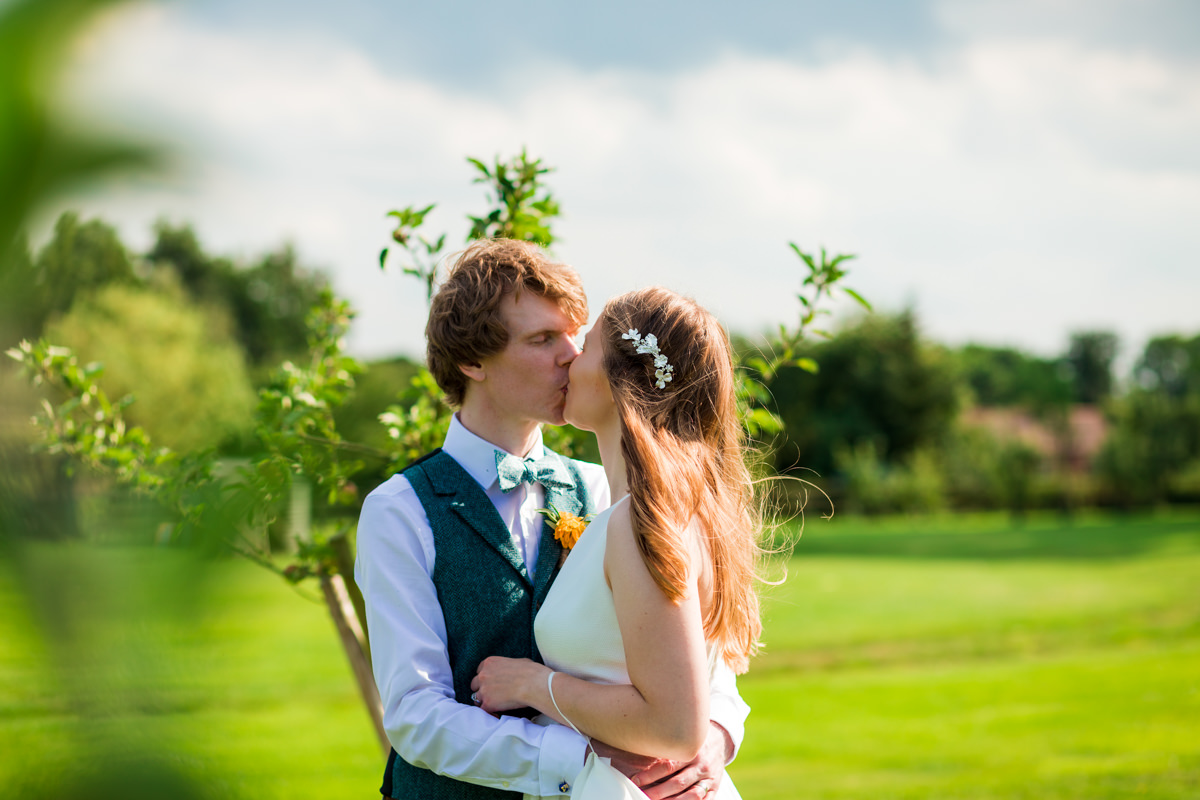 Bride and groom kissing in sun on green field