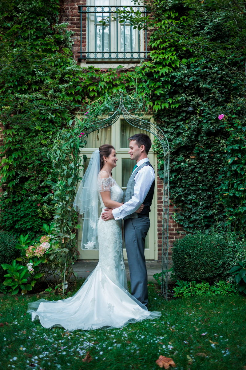 bride and groom standing in front of ivy