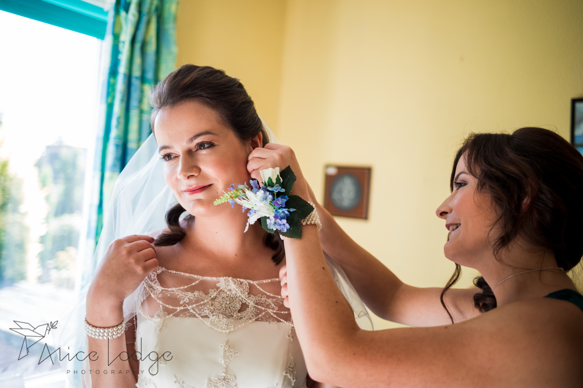 sister putting brides earring in