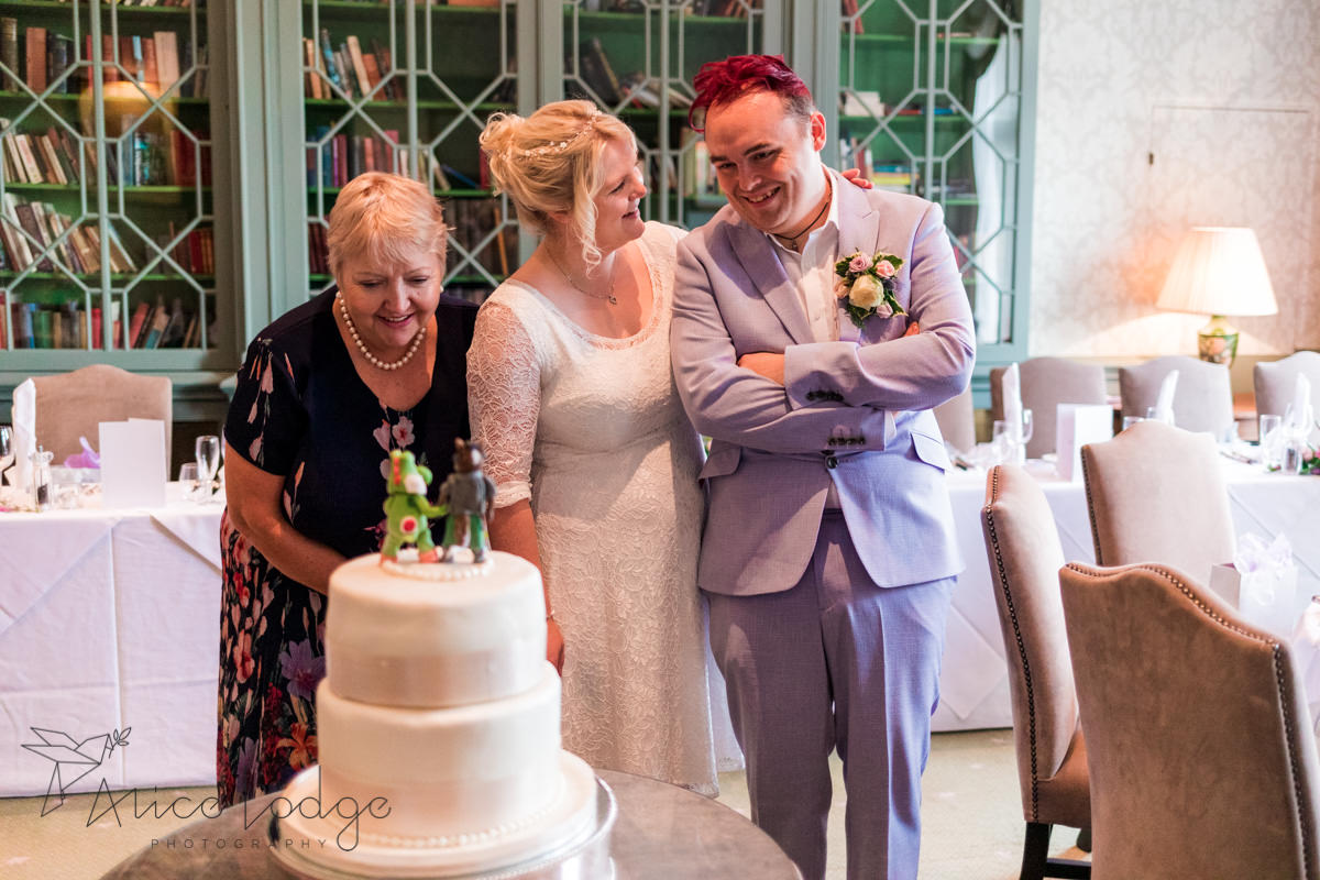 wedding couple smiling at wedding cake