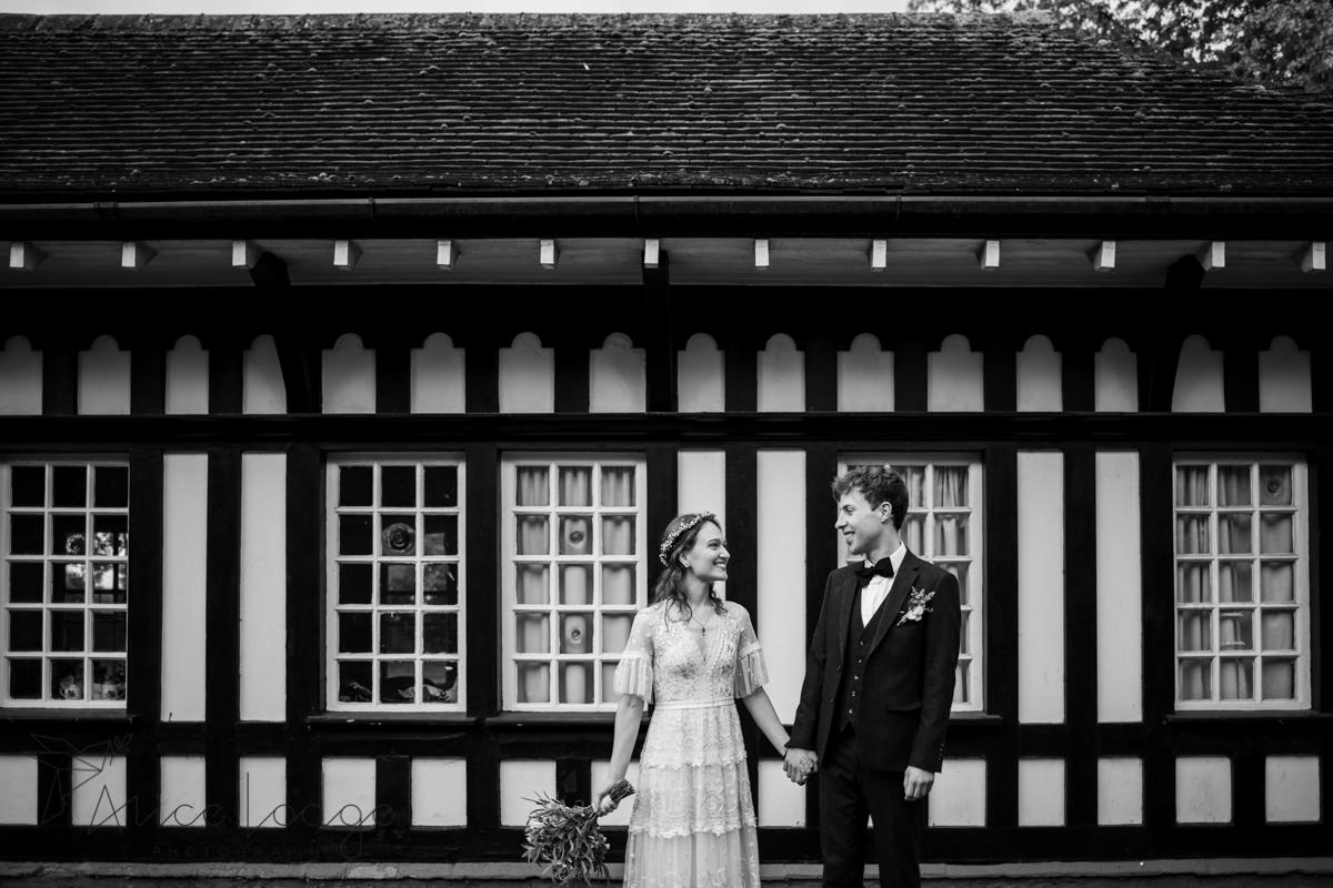bride and groom in front of old house