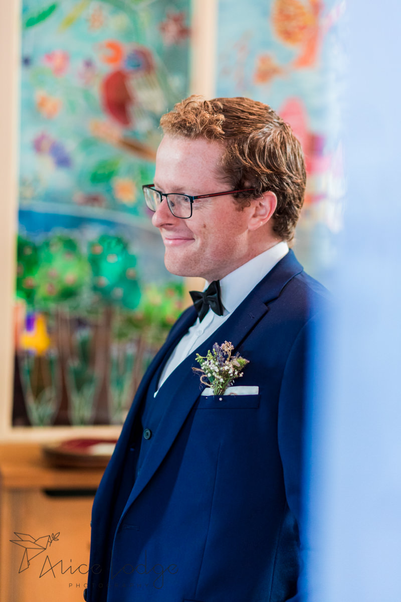 groomsman in blue suit smiling