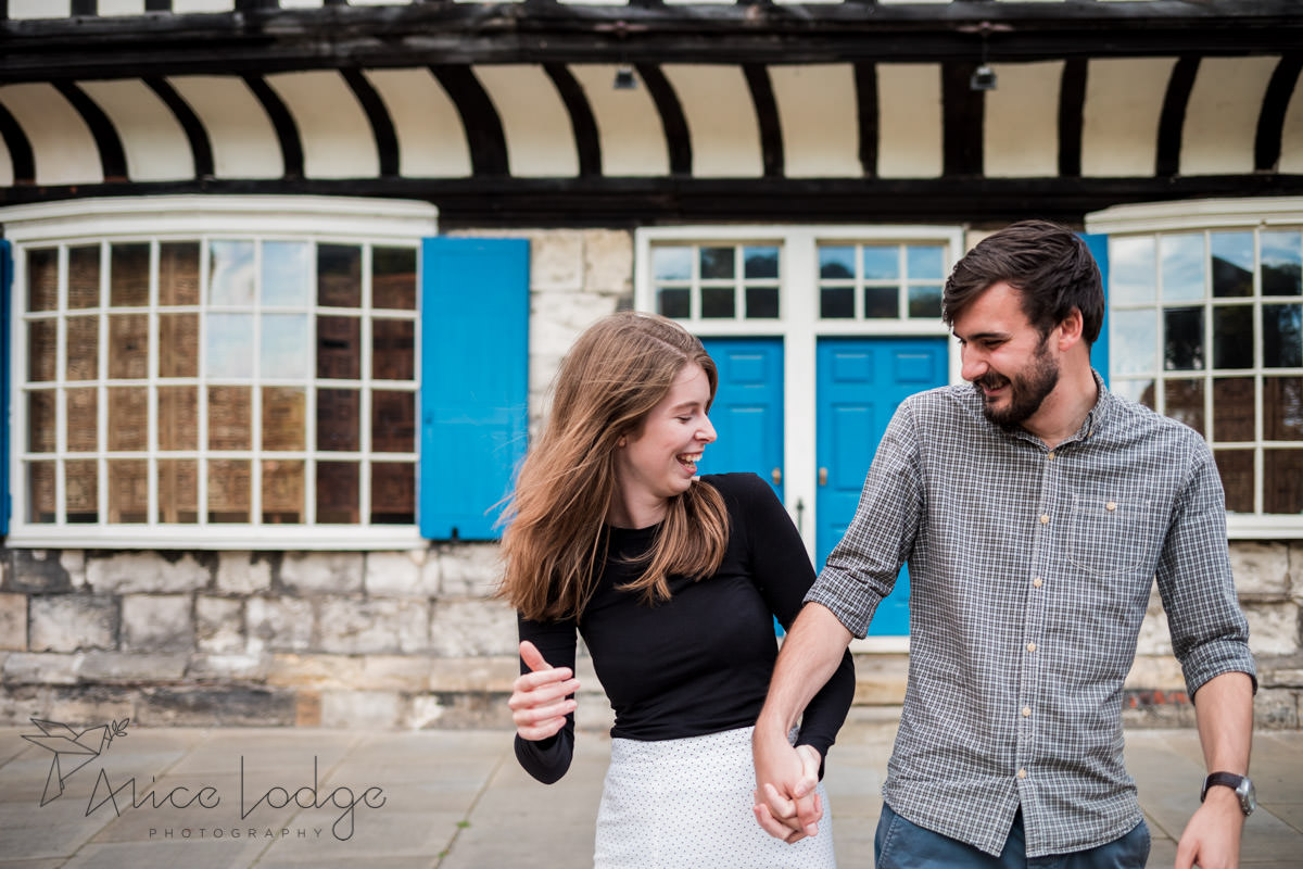 Man and woman laughing in front of blue door in York