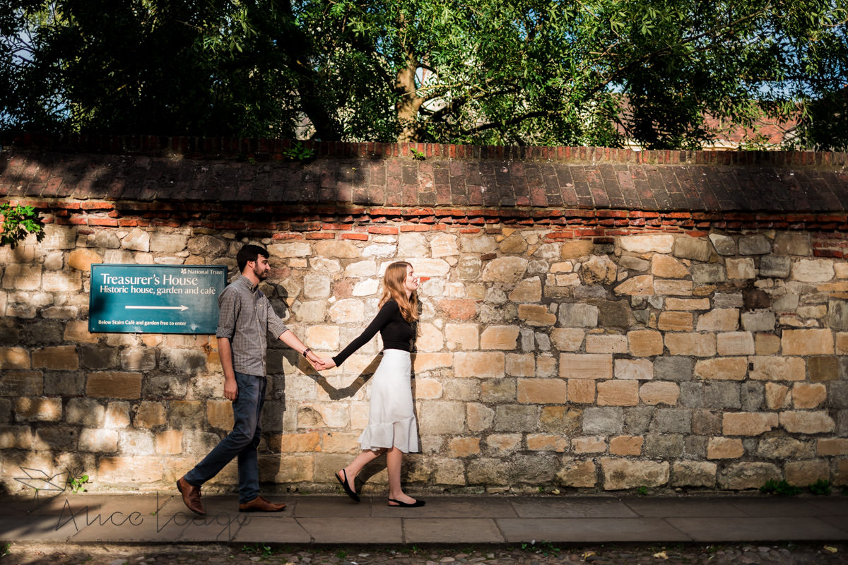 Man and woman walking along stone wall in front of York Minster