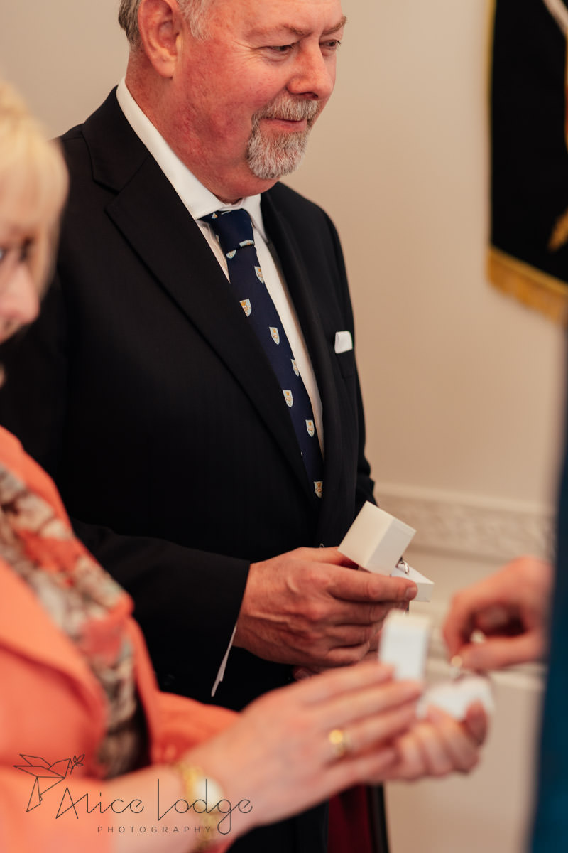 father of bride holding rings