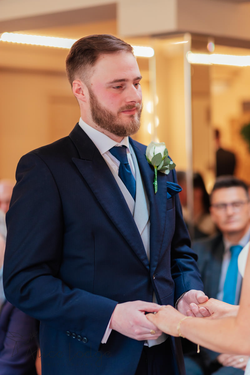 groom with blue suit during wedding ceremony