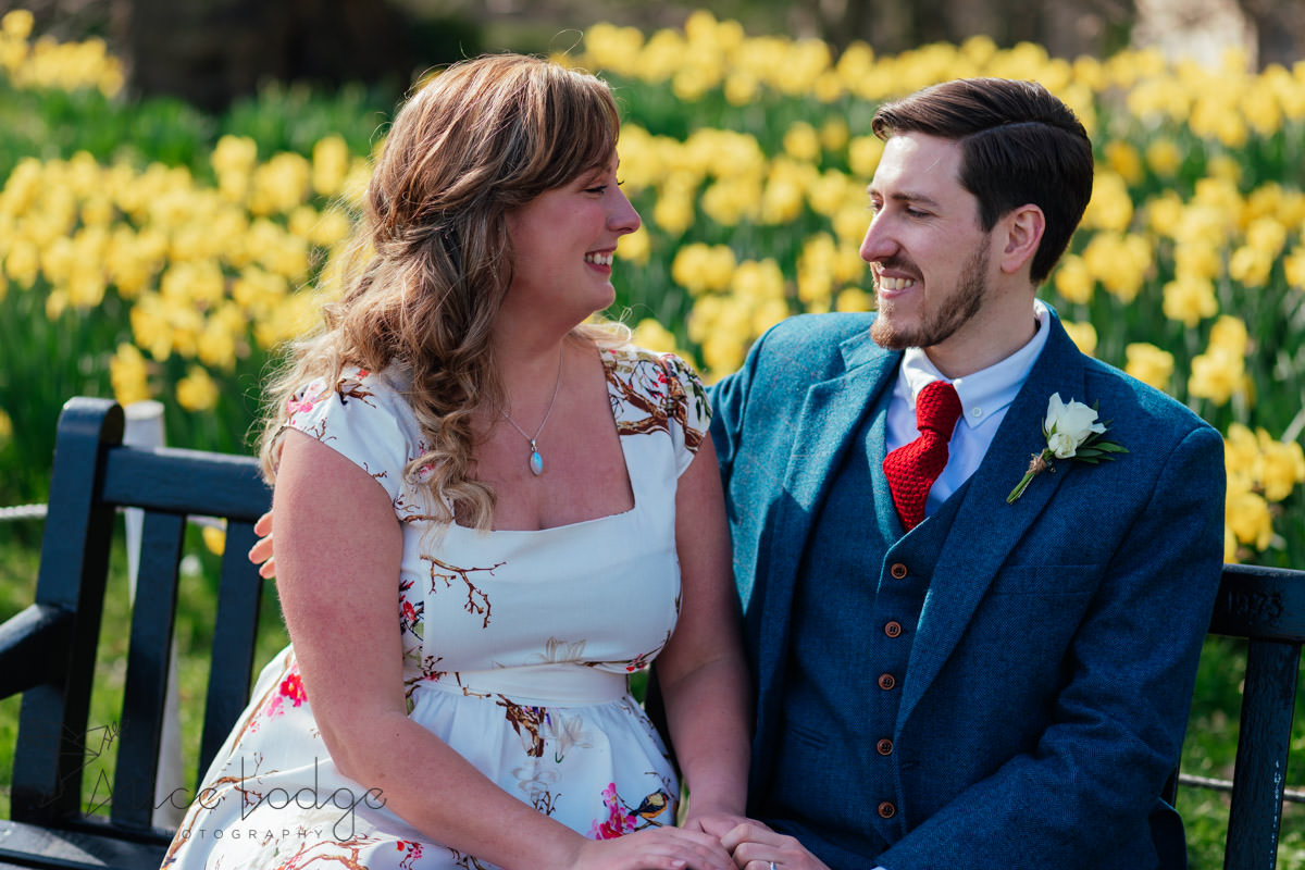 bride and groom in front of daffodils at york museum gardens
