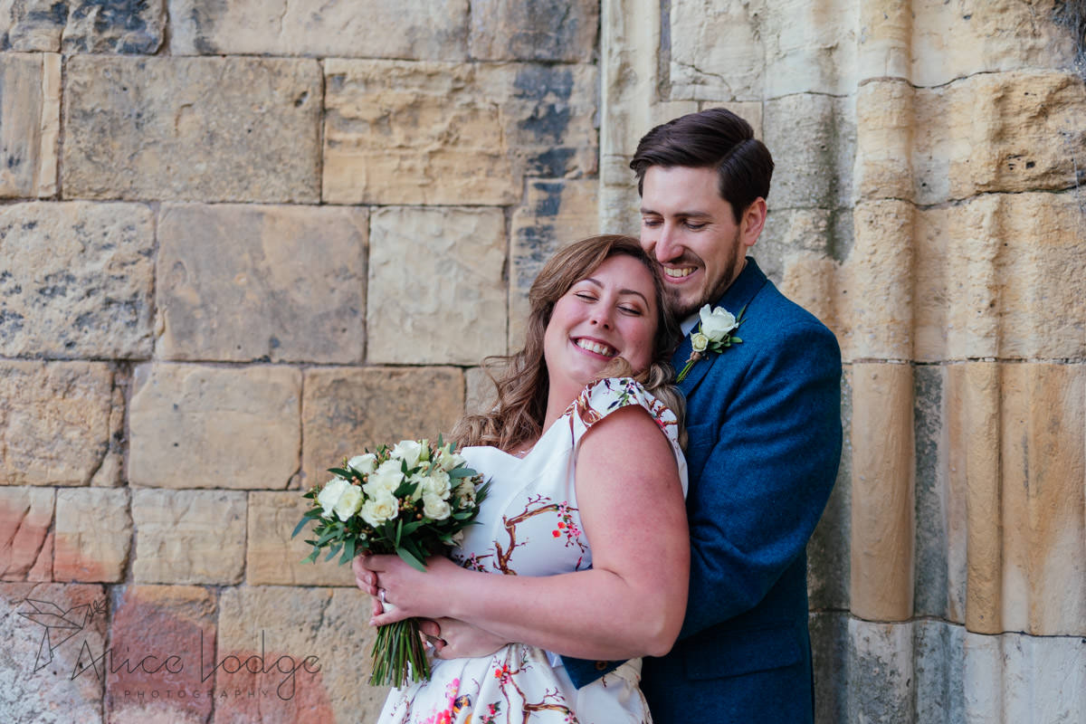 bride and groom in front of daffodils at york st Mary's abbey