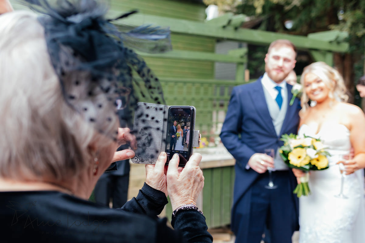 grandmother taking picture of wedding couple