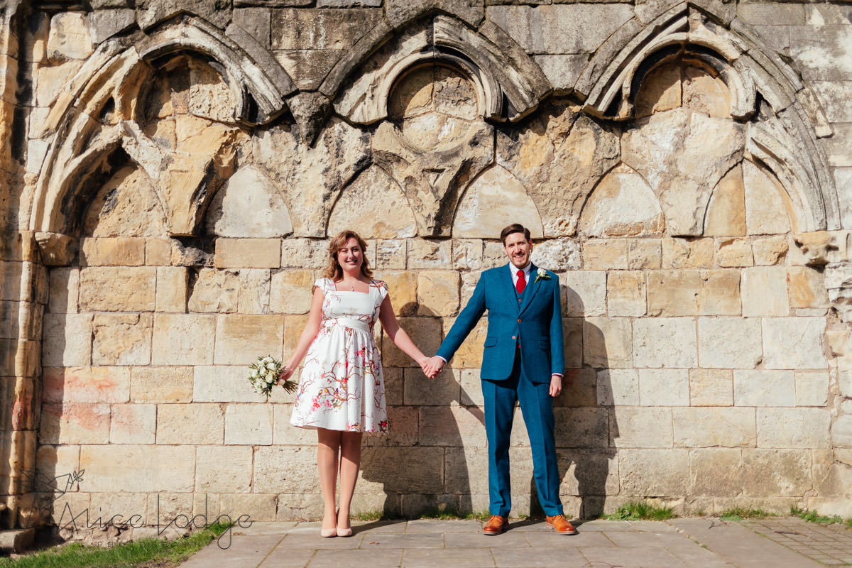 bride and groom in sunshine in front of old york wall