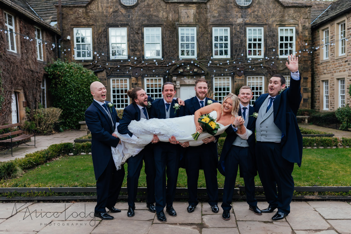 groomsmen lifting up bride