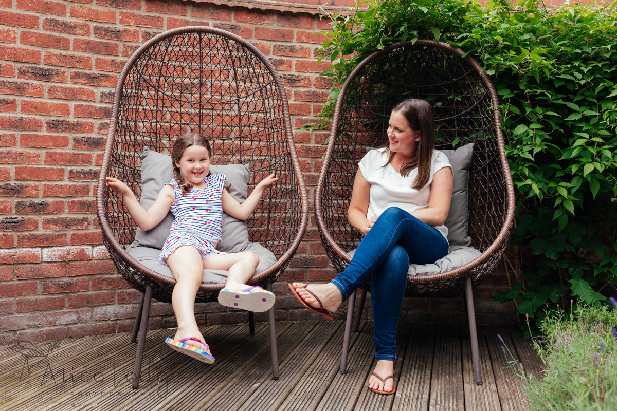 mother and daughter in garden chairs