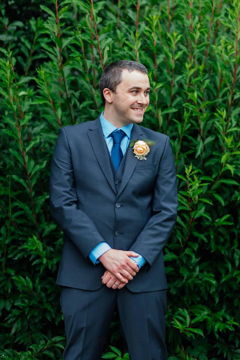 groom in front of hedge